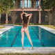 nude, back, ass, hands on head, swimming pool, high heels, palms, tropical, curly hairs wallpaper