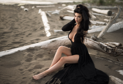 sitting, black dress, cleavage, sand, looking away, beach, legs, boobs, brunette wallpaper